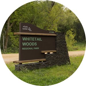 "Brown sign on the side of the road that says ""Whitetail Woods Regional Park"""